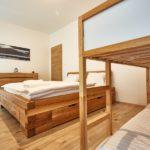 Ložnice s manželskou postelí a palandou apartmánu A1